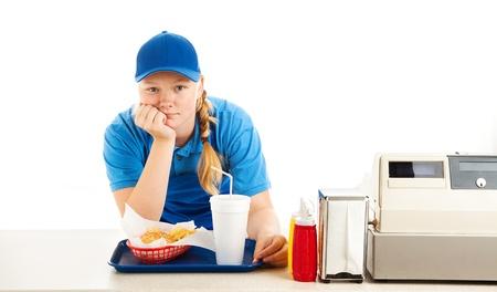 caja registradora: Trabajador adolescente en un restaurante de comida rápida aburrido y apoyado en el mostrador. Fondo blanco.