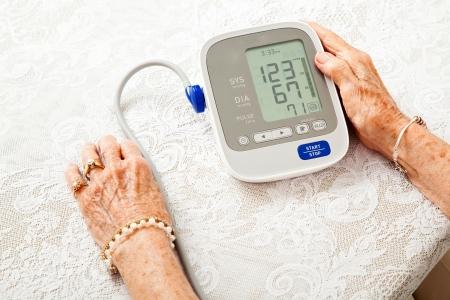 ホーム メーターに彼女の血圧をチェック、年配の女性の手のクローズ アップ。結果は低いです。