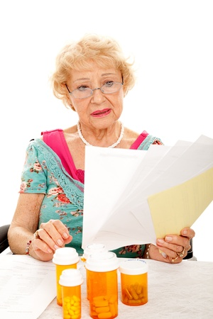 medical bills: Disabled senior lady in wheelchair holding a pile of medical bills.  White background.