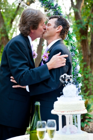 Two grooms kissing each other at their wedding reception.