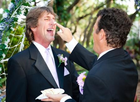 boda gay: Un novio pone juguetonamente pastel de bodas en la nariz de su esposo en su boda. Foto de archivo