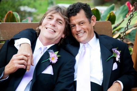Beau couple gay de détente sur une balançoire à leur réception de mariage.
