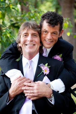 야외 결혼식 초상화를 위해 포즈를 취하는 사랑에 잘 생긴 게이 커플.