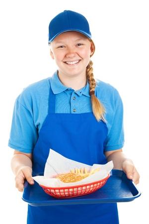 ハンバーガーとフライド ポテトを提供 10 代のファーストフードの労働者。 白で隔離。  写真素材