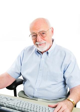 Senior man sitting at a desktop computer.  Isolated on white. photo