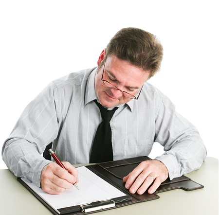 Businessman looking down and taking notes on a legal pad.  White background. photo