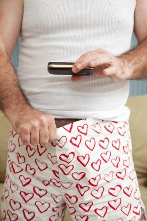 """pene: Hombre sexting una imagen de su """"salchicha"""", o el pene con su teléfono celular. Foto de archivo"""