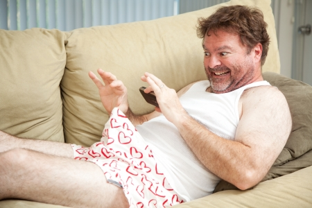 Humorous photo of a man in his underwear, using his cellphone to send a picture of his penis.   photo
