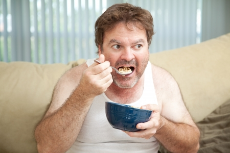 eating breakfast: Unemployed man sitting on the couch eating cereal as he watches television.