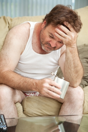 Unemployed middle-aged man is hopeless and turns to drinking.   photo