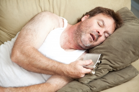 wifebeater: Unemployed man passed out drunk on the couch with a flask of booze in his hand.