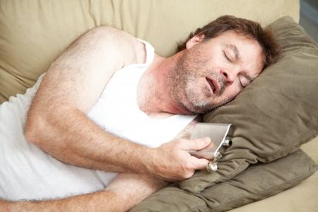 wifebeater: Uomo disoccupato svenuto ubriaco sul divano con una bottiglia di alcool in mano.