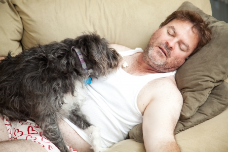 lazy: Unemployed man passed out on the couch in his underwear.  His dog is eating popcorn from his chest.