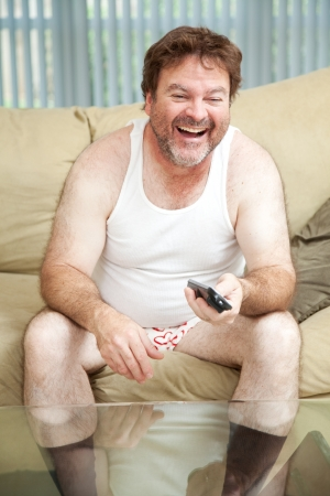 Unemployed man laughing and watching a funny show on television.