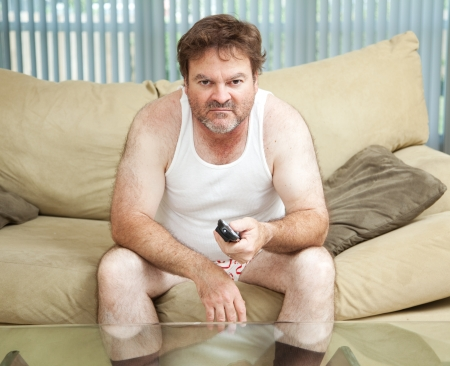Unemployed man sitting home watching TV, bored and discouraged.   photo