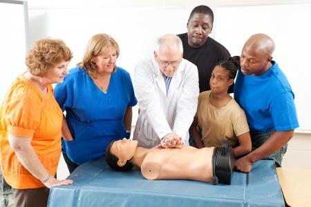 primeros auxilios: M�dico demuestra CPR y la clase de educaci�n de adultos en primeros auxilios.