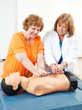 chest compression: Doctor teaches adult education student how to perform CPR.