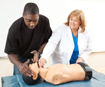 Doctor teaching Cardiopulmonary resuscitation to an adult african-american student.   Stock Photo