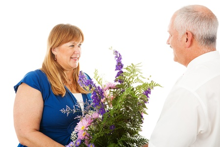 devoted: Happy wife receives flowers from her devoted husband.  Isolated on white.