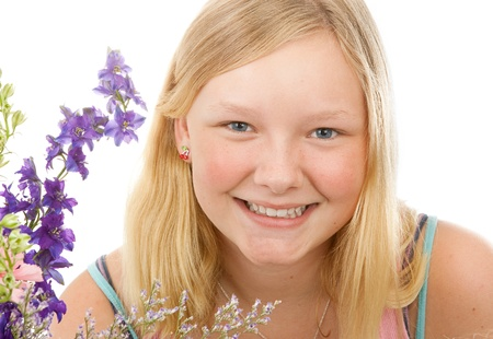 no teeth smile: Portrait of a beautiful blond, blue-eyed teenage girl with flowers, on a white background.
