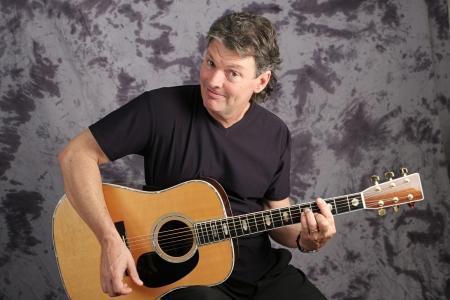 Handsome mature musician playing his guitar.  Studio portrait.