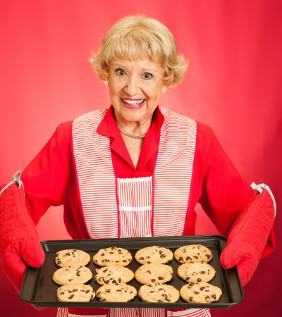 cookie sheet: Sweet pretty grandmother holding a tray of freshly baked chocolate chip cookies