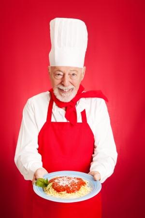 marinara: Handsome Italian chef cooks spaghetti marinara   Red background