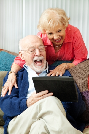 retirement couple: Senior couple having fun and laughing while using their tablet pc computer