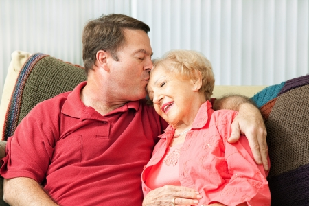 Senior woman gets a kiss from her loving adult son who has come to visit her in the nursing home
