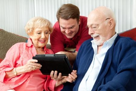 새로운 태블릿 PC 컴퓨터를 사용하기 위해 자신의 부모를 가르치는 성인 아들