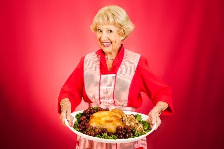 Douce grand-mère tenant un repas de dinde cuite magnifiquement. Banque d'images