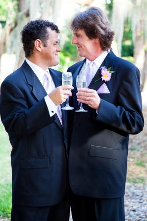 boda gay: Gay Pareja brindando con champán en su boda.