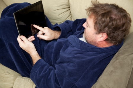 A man at home on his couch using this tablet PC. Stock Photo - 22482825