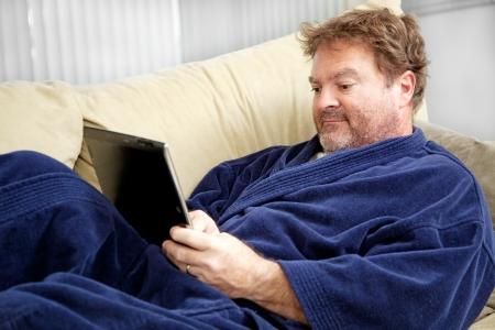 초라한 자신의 태블릿 PC를 사용하여 자신의 목욕 가운에 집에 앉아 실업자 남자를 찾고.