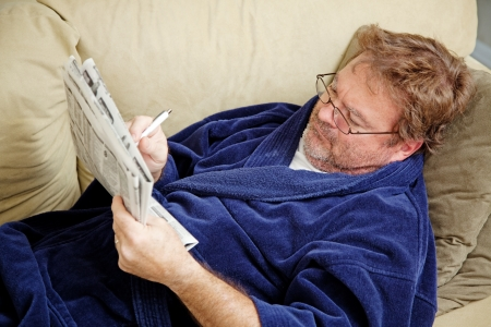house robes: Unemployed man checking the classified section of the newspaper for job opportunities.  Could also be doing crossword puzzle Stock Photo