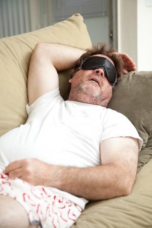 Faul, arbeitsloser Mann schlafend auf der Couch, unrasiert und in seiner Unterwäsche.