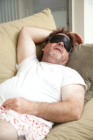 Lazy, unemployed man asleep on the couch, unshaven and in his underwear.   Stock Photo