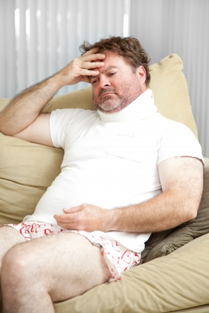Man home from work with a long term injury, worrying about paying the bills.   Stock Photo
