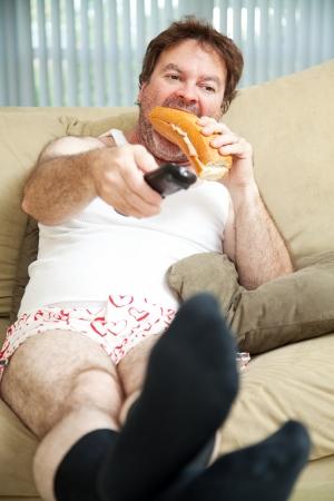 Chômeur assis sur le canapé dans ses sous-vêtements, en regardant la télévision et en mangeant un sandwich.