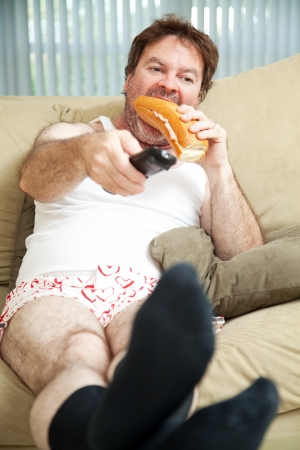 Unemployed man sitting on the couch in his underwear, watching TV and eating a sandwich.