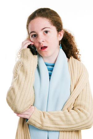 Cute latina tween teenage girl talking on the phone with shocked expression.  Isolated on white.