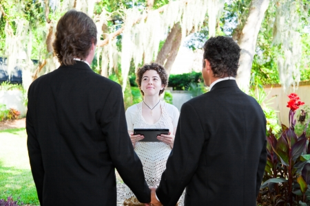 marriage ceremony: Young female minister uses a tablet PC to perform a gay marriage ceremony.