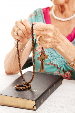 Closeup of senior womans hands as she says the rosary.   photo