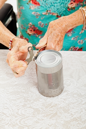 Closeup of senior woman's hands as she struggles to open a can with her painful arthritis. Stock Photo - 22482855