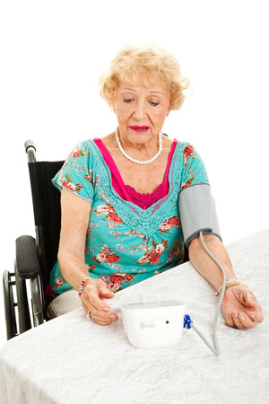 Senior woman taking her own blood pressure at home, worried about the results.  Isolated on white.