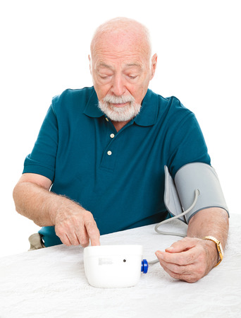 sphygmomanometer: Senior man checking his blood pressure at home.  Isolated on white.   Stock Photo