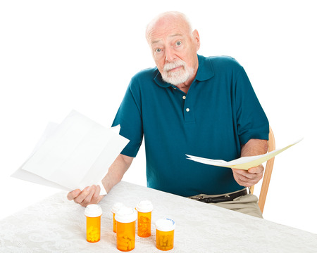 Senior man doesn't know how he will pay all his medical bills.  Isolated on white.   Stockfoto