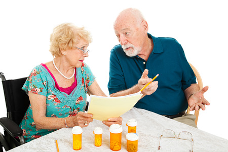 Senior couple at the dining room table discussing medical and prescription costs.  White background.   photo