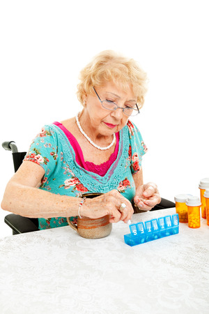 Senior woman in wheelchair sorting her medication for the week.  White background.   photo