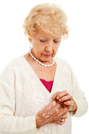 Senior woman struggles to button her sweater because of painful arthritis.  Isolated on white.